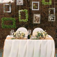 Необычное оформление стены за женихом и невестой тюками сена и  декоративными рамками для фотографий