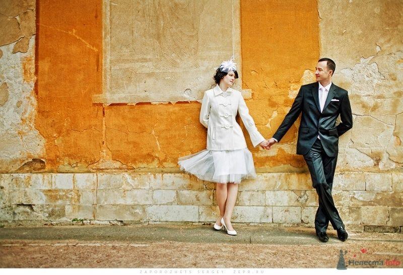 Жених и невеста, взявшись за руки, стоят у оранжевого здания - фото 30891 Фотограф Запорожец Сергей