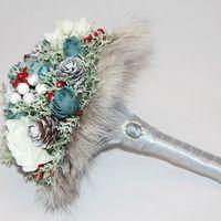 Роскошный свадебный букет невесты в зимнем стиле.  Темно-синие розы, декоративный мох и белоснежные цветы гортензии создают спокойный фон для сочных и ярких ягод.  Натуральный мех по контуру придает воздушность и изысканность.  Ножка букета оформлена атла