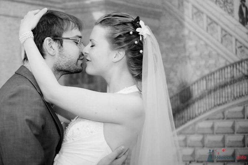 Жених и невеста стоят, прислонившись друг к другу, на фоне серого дома
