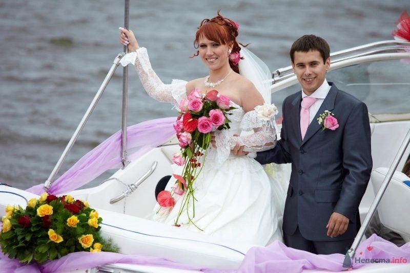 Жених и невеста стоят на палубе катера, прислонившись друг к другу,