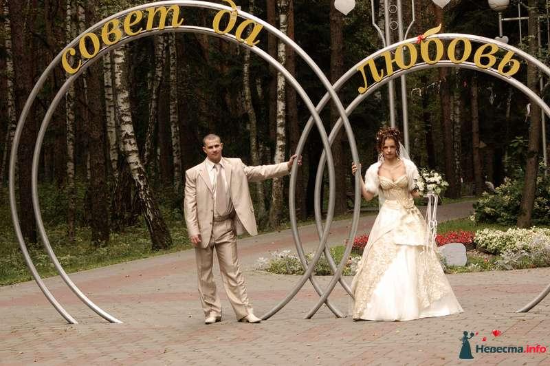 Жених и невеста стоят в парке под высокими металлическими кольцами - фото 81267 Любимка)