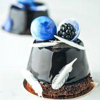 Мусовый десерт в глясаже украшенный шоколадными полусферами и пёрышками из белого шоколада ,и маленький освежающий акцент в виде ягоды ежевики.