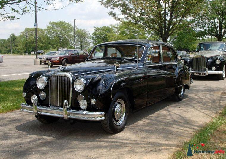"""Черный """"Rolls-Royce"""" на фоне  автостоянки."""