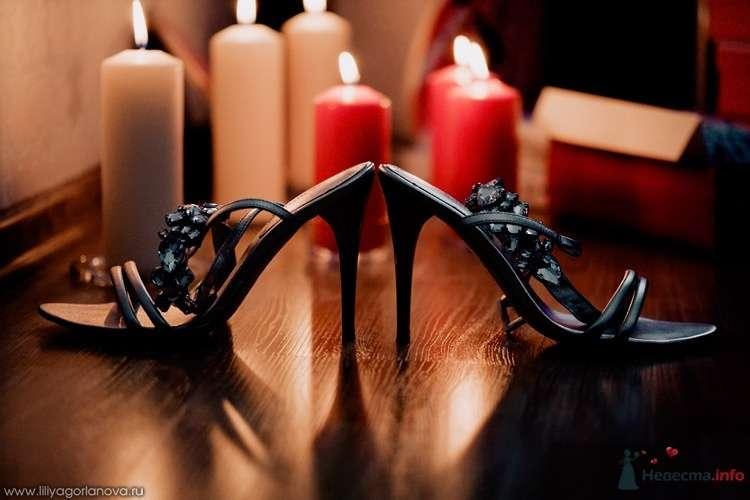 Черные босоножки  на высокой шпильке, украшенные камнями стоят возле зажженных свеч. - фото 69446 Вашкетова Юлия - организатор свадеб, флорист.