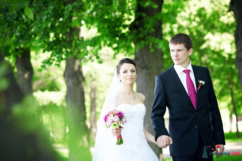 Жених и невеста, взявшись за руки, идет по парку