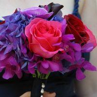 Яркий букет невесты из ярко-красных и розовых роз, синих гортензий и ярко-сиреневых орхидей, декорированный темно-синей лентой и белыми бусинами