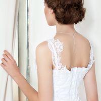 Свадебное платье Magdalena  Свадебное платье с многослойной фатиновой юбкой на подкладке. Последний слой фатина понизу отделан кружевом, от талии спускаются многочисленные вставки из разноуровневого фатина. Лиф корсетного типа из атласа, поверх идет сетка