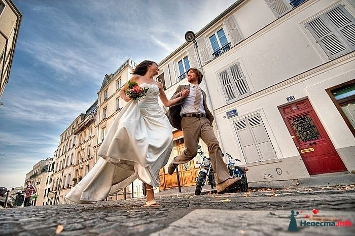 Жених и невеста, взявшись за руки, бегут по улице