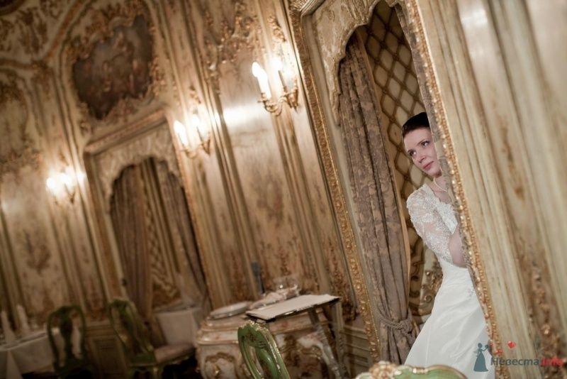 Невеста в белом платье стоит у двери в комнате - фото 53721 ларина т