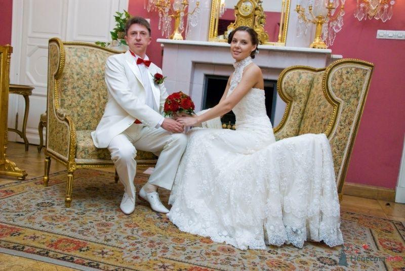 Жених и невеста, взявшись за руки, сидят на креслах у камина - фото 48758 katsonya