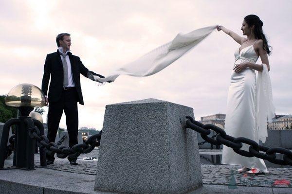 Жених и невеста стоит на площади и держат в руках вуаль - фото 45623 OlgaTimkina