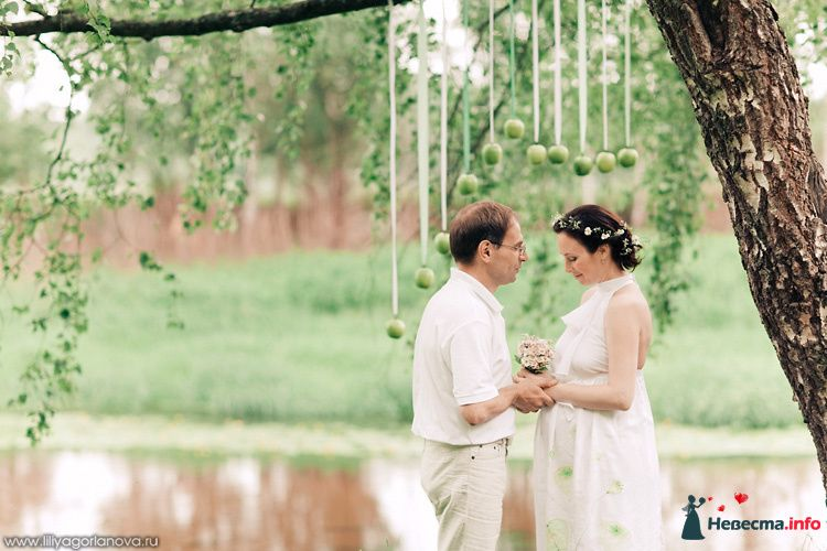 Жених и невеста, взявшись за руки, стоят возде дерева в саду - фото 98559 Chanel№5