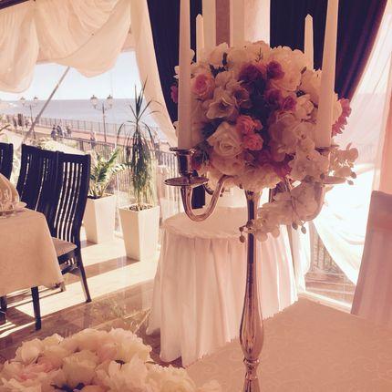 Канделябр со свечами и цветочной композицией в оформлении зала