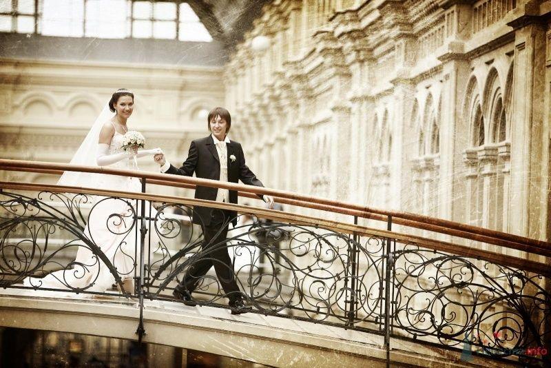 Жених и невеста, взявшись за руки,   идут по мосту