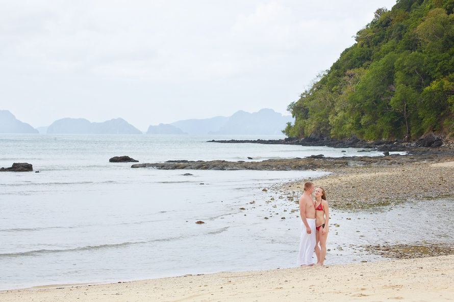 На побережье отдыхают влюбленные, парень в белых брюках обнимает за талию девушку в красном купальнике, она смотрит ему в глаза - фото 2258344 Свадебный фотограф Марина Лонгортова