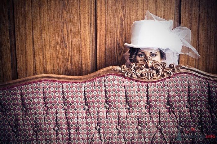 На голове невесты белый цилиндр с бантом из фатина